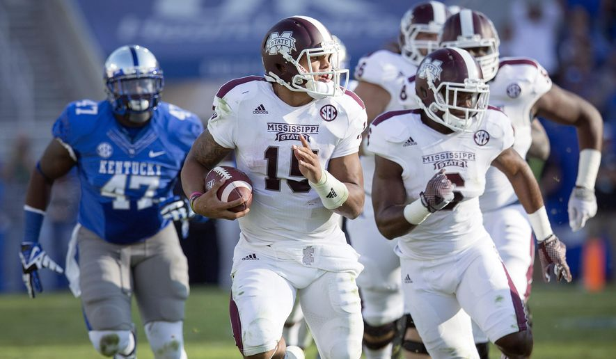 Mississippi State quarterback Dak Prescott, center, runs for a first down during the first half of an NCAA college football game against Kentucky at Commonwealth Stadium in Lexington, Ky., Saturday, Oct. 25, 2014. (AP Photo/David Stephenson)