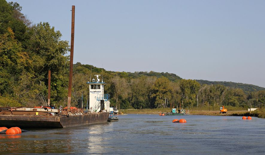 FOR RELEASE SATURDAY, OCTOBER 25, 2014, AT 12:01 A.M. CDT - In this Sept. 25, 2014 photo, a black pipeline, supported by orange buoys, runs from the dredge, toward back at center, past transport barge, left, at the site of the U.S. Army Corps of Engineers' project Hole-in-the-Rock, near Macy, Neb. The project's goal is to repair damages to existing shallow water habitat, due to damages caused by the Missouri River flooding in 2011. (AP Photo/The Sioux City Journal, Dawn J. Sagert)