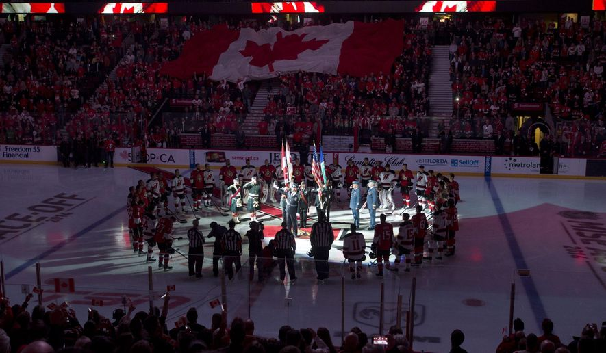 Anthem singer Lyndon Slewidge holds up the microphone as the crowd sings 'O Canada' before the NHL hockey game between the Ottawa Senators and New Jersey Devils, Saturday, Oct. 25, 2014 in Ottawa, Ontario. (AP Photo/The Canadian Press, Adrian Wyld)