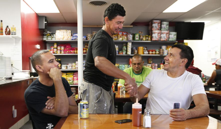 FOR RELEASE SATURDAY, OCTOBER 25, 2014, AT 9:00 A.M. EDT - In this Oct. 15, 2014 photo, from left, Reginaldo Matias, Amilton Penheiro Da Silva, and Rinaldo Gonzales bid each other farewell after their lunch at Cantinho Do Brasil in Richmond, Va. (AP Photo/Richmond Times-Dispatch, Dean Hoffmeyer)