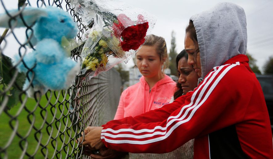 Marysville Pilchuck student Tyanna Davis, right, places flowers on the fence bordering Marysville Pilchuck High School in Marysville, Wash., Saturday, Oct. 25, 2014. A student opened fire in a high school cafeteria north of Seattle on Friday, killing at least one person and shooting several others in the head, officials said. The gunman also died in the attack. (AP Photo/The Herald, Mark Mulligan)