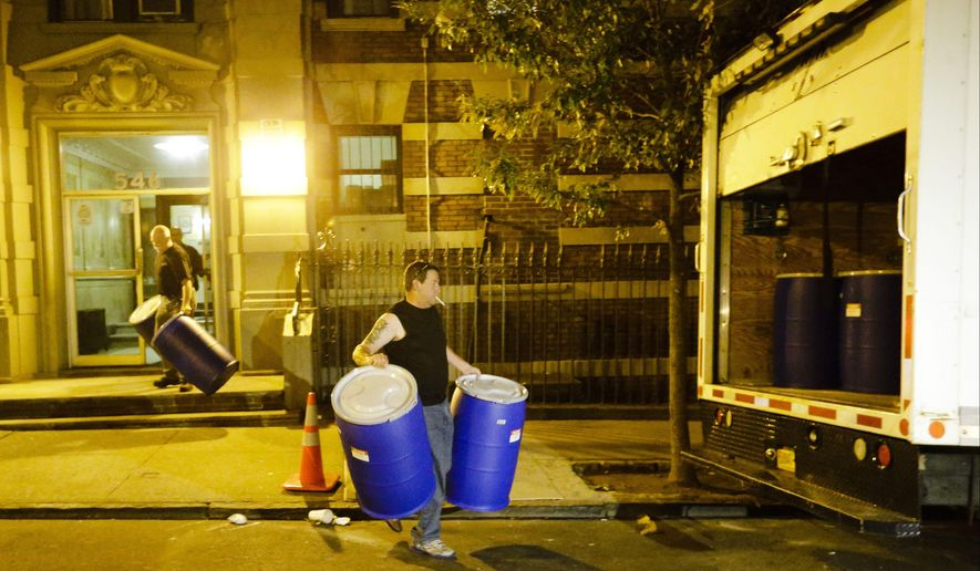 Workers from BioRecoveryCorp carry barrels from the apartment building of Ebola patient Dr. Craig Spencer Friday, Oct. 24, 2014, in New York. Spencer remained in stable condition while isolated in a hospital, talking by cellphone to his family and assisting disease detectives who are accounting for his every movement since arriving in New York from Guinea via Europe on Oct. 17. (AP Photo/Frank Franklin II)