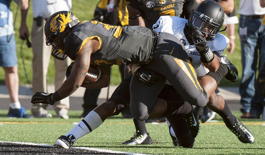 Missouri running back Russell Hansbrough, left, scores a touchdown as he gets past Vanderbilt's Taurean Ferguson during the second quarter of an NCAA college football game Saturday, Oct. 25, 2014, in Columbia, Mo. (AP Photo/L.G. Patterson)