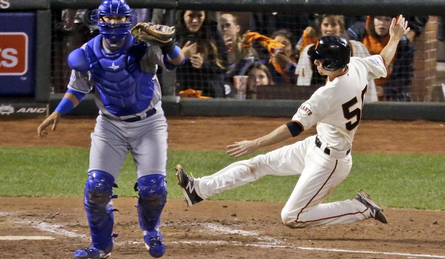 San Francisco Giants' Matt Duffy scores on a hit by Buster Posey as Kansas City Royals' catcher Salvador Perez waits for the throw during the third inning of Game 4 of baseball's World Series against the Kansas City Royals on Saturday, Oct. 25, 2014, in San Francisco.(AP Photo/Charlie Riedel)