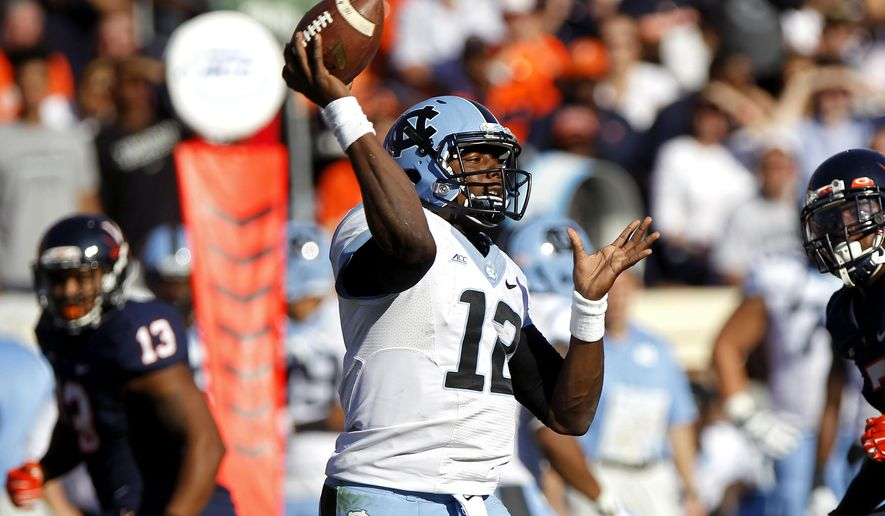North Carolina quarterback Marquise Williams (12) throws a pass during the fourth quarter of an NCAA football game against Virginia in Charlottesville, Va., Saturday, Oct. 25, 2014. (AP Photo/The Daily Progress, Ryan M. Kelly)