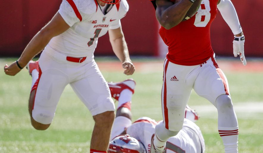 Nebraska running back Ameer Abdullah (8) runs away from Rutgers place kicker Kyle Federico (1) and wide receiver Vance Matthews (87) on a kickoff return in the second half of an NCAA college football game in Lincoln, Neb., Saturday, Oct. 25, 2014. Nebraska won 42-24. (AP Photo/Nati Harnik)