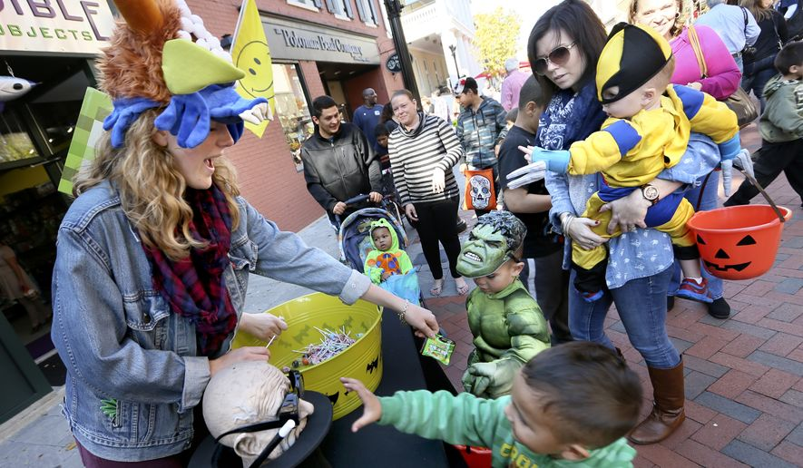 Blaire Collingwood, left, hands out candy to trick or treaters on Sat. Oct. 25, 2014, during the Old Town Winchester, Va. Halloween Spooktacular event. (AP Photo/The Winchester Star, Ginger Perry) ** FILE **