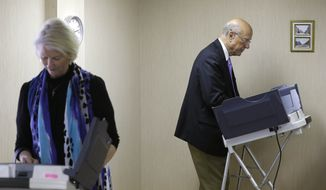 Sen. Pat Roberts, R-Kan., right, casts his ballot with his wife Franki, left, during early voting at the Ford County Elections Office in Dodge City, Kan., Friday, Oct. 24, 2014. (AP Photo/Orlin Wagner)