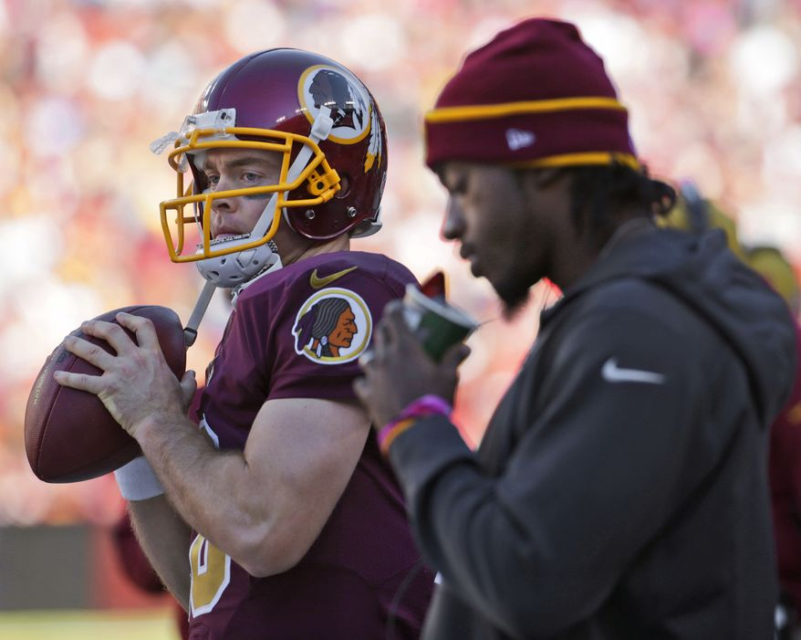 Washington Redskins quarterbacks Colt McCoy, left, and Robert Griffin III, right, on the sidelines during the second half of a NFL football game against the Tennessee Titans, Sunday, Oct. 19, 2014. at Fedex Field in Landover, MD. (AP Photo/Pablo Martinez Monsivais)