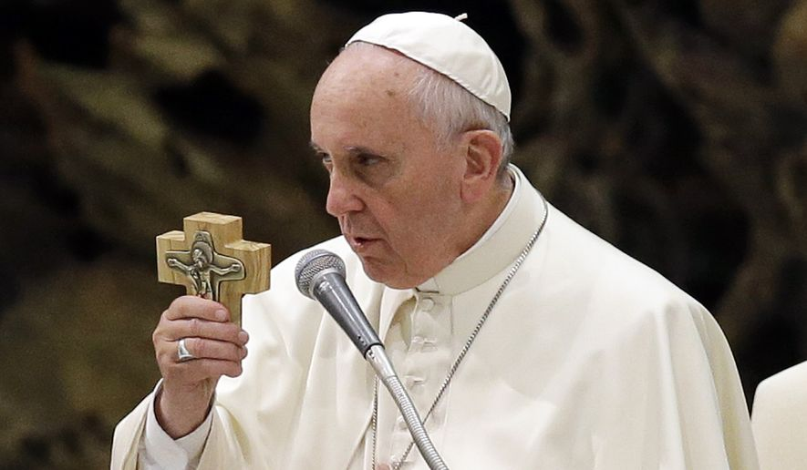 Pope Francis holds a cross during a meeting with members of the Schoenstatt movement at the Vatican, Saturday, Oct. 25, 2014. (AP Photo/Gregorio Borgia)