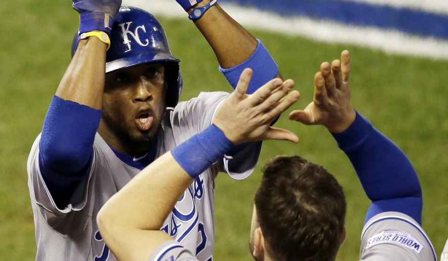 Kansas City Royals' Alcides Escobar is congratulated by teammate Mike Moustakas after scoring during the sixth inning of Game 3 of baseball's World Series against the San Francisco Giants Friday, Oct. 24, 2014, in San Francisco. (AP Photo/Eric Risberg)