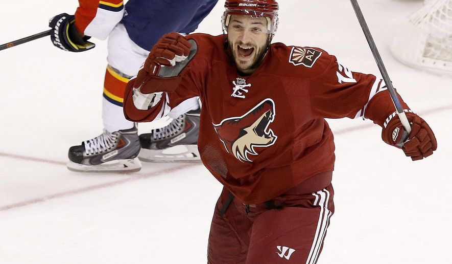Arizona Coyotes' Justin Hodgman (12) celebrates his goal as Florida Panthers' Scottie Upshall (19) skates away during the third period of an NHL hockey game Saturday, Oct. 25, 2014, in Glendale, Ariz.  The Coyotes defeated the Panthers 2-1 in overtime. (AP Photo/Ross D. Franklin)