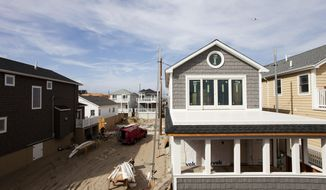 In this Oct. 15, 2014, photo, new homes are under construction in the Breezy Point section of the Queens borough of New York, replacing those that burned to the ground two years before during Superstorm Sandy. The new homes are built on raised concrete foundations, placing them above future flooding. (AP Photo/Mark Lennihan)
