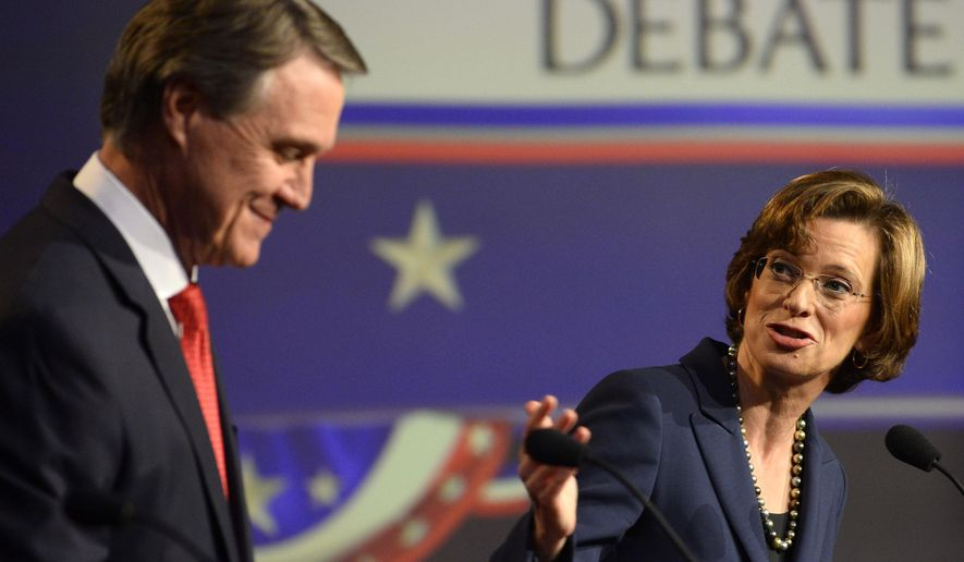 Democratic Georgia U.S. Senatorial candidate Michelle Nunn, right, asks Republican candidate David Perdue about outsourcing jobs during an Atlanta Press Club debate at the Georgia Public Broadcasting studios Sunday, Oct. 26, 2014, in Atlanta. (AP Photo/David Tulis)