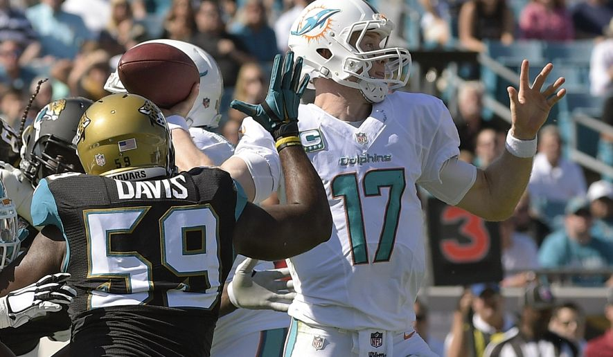 Miami Dolphins quarterback Ryan Tannehill (17) throws a pass as he is pressured by Jacksonville Jaguars defensive end Ryan Davis (59) during the first half of an NFL football game in Jacksonville, Fla., Sunday, Oct. 26, 2014. (AP Photo/Phelan M. Ebenhack)