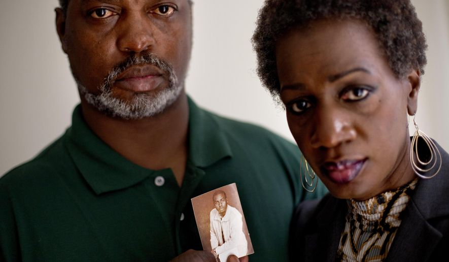 FILE- In this May 23, 2012 file photo, Pam Champion, right, and Robert Champion, Sr., left, hold a photo of their son, Robert, a Florida A&M University drum major who died in a hazing incident, as they are photographed in their attorney's office following a press conference in Atlanta.  The trial for four band members charged in the hazing death of Champion begins Monday, Oct. 27, 2014 in Orlando, Fla.(AP Photo/David Goldman, File)