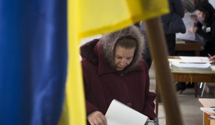 A woman casts her ballot during parliament elections at a polling station in Volnovakha, a village on the front line of fighting between Ukrainian government forces and rebels, eastern Ukraine, Sunday, Oct. 26, 2014. Voters in Ukraine headed to the polls Sunday to elect a new parliament, overhauling a legislature tainted by its association with ousted President Viktor Yanukovych. (AP Photo/Dmitry Lovetsky)