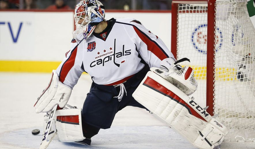 Washington Capitals goalie Braden Holtby kicks away a shot from the Calgary Flames during the third period of an NHL hockey game Saturday, Oct. 25, 2014, in Calgary, Alberta. (AP Photo/The Canadian Press, Jeff McIntosh)
