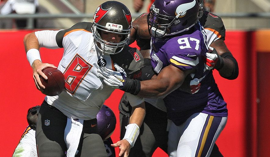 Minnesota Vikings defensive end Everson Griffen (97) sacks Tampa Bay Buccaneers quarterback Mike Glennon (8) during the second quarter of an NFL football game Sunday, Oct. 26, 2014, in Tampa, Fla. (AP Photo/Reinhold Matay)