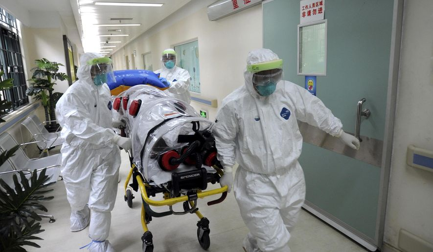 In this Oct. 23, 2014 photo, medical workers wearing protective suits, handle a protective stretcher as they conduct a training exercise on dealing with suspected Ebola cases at a hospital in Guangzhou in south China's Guangdong province. The longer the Ebola outbreak rages in Africa, the greater chance a traveler infected with the virus touches down in an Asian city. How quickly any case is detected - and the measures taken once it is - will determine whether the virus takes hold in a region where billions live in poverty and public health systems are often very weak. (AP Photo) CHINA OUT