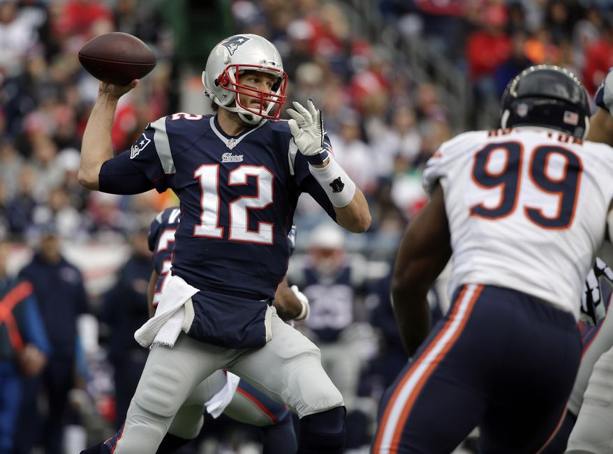 New England Patriots quarterback Tom Brady (12) passes over Chicago Bears defensive end Lamarr Houston (99) in the first half of an NFL football game on Sunday, Oct. 26, 2014, in Foxborough, Mass. (AP Photo/Steven Senne)