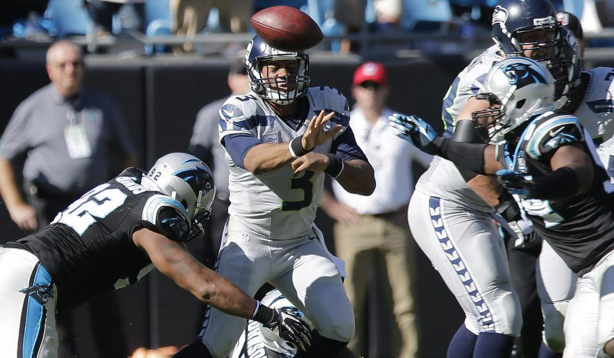 Seattle Seahawks quarterback Russell Wilson (3) passes the ball under pressure from Carolina Panthers defensive tackle Dwan Edwards (92) during the second half of an NFL football game, Sunday, Oct. 26, 2014, in Charlotte. (AP Photo/Chuck Burton)