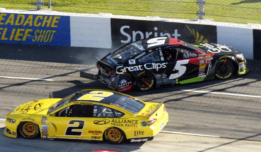 Brad Keselowski (2) passes Kasey Kahne (5) during the NASCAR Sprint Cup Series auto race at Martinsville Speedway in Martinsville, Va., Sunday, Oct. 26, 2014. (AP Photo/Don Petersen)