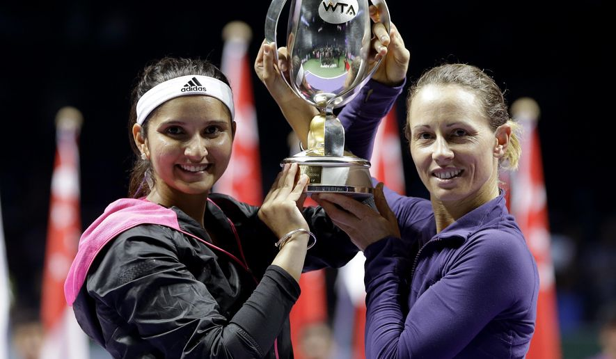 India's Sania Mirza, left, and Zimbabwe's Cara Black hold their trophy aloft after defeating Taiwain's Hsieh Su-Wei and China's Peng Shuai in the doubles final at the WTA tennis finals in Singapore, Sunday, Oct. 26, 2014. (AP Photo/Mark Baker)