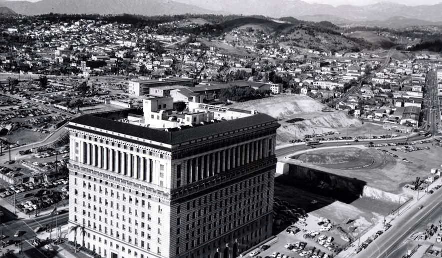 FILE - This Jan. 12, 1951 file photo shows a view of the Los Angeles Hall of Justice with the Hollywood Freeway (U.S. Highway 101) under construction behind it. The Hall of Justice opened in 1926 as an all purpose justice center, providing 17 courtrooms, 750 jail cells, a morgue and offices for law enforcement officials. Its proximity to Hollywood made it a site of famous trials and fictional movie and TV shows. After decades of service and two decades of disuse after a 1994 earthquake, the Hall of Justice has been returned to its former, albeit repurposed, glory. (AP Photo/File)