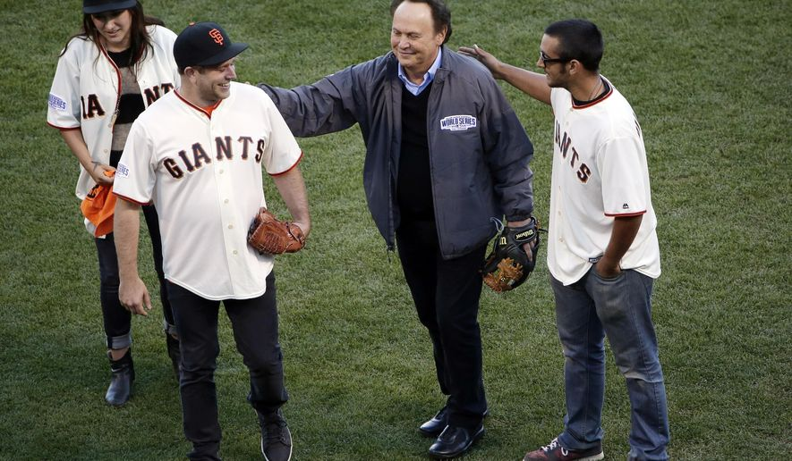 Robin Williams son, Zak Williams, second from left, gets a pat on the back from Billy Crystal after Zak threw out the ceremonial first pitch as his siblings Zelda, left, and Cody look on before Game 5 of baseball's World Series between the Kansas City Royals and the San Francisco Giants on Sunday, Oct. 26, 2014, in San Francisco. (AP Photo/Marcio Jose Sanchez)