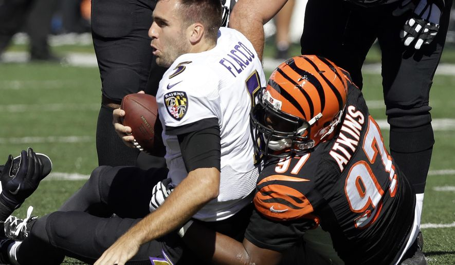 Baltimore Ravens quarterback Joe Flacco, left, is wrapped up by Cincinnati Bengals defensive tackle Geno Atkins after losing his helmet during the first half of an NFL football game in Cincinnati, Sunday, Oct. 26, 2014. (AP Photo/Al Behrman)