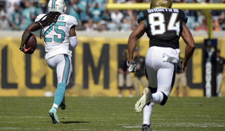 Miami Dolphins free safety Louis Delmas (25) returns an intercepted pass 81-yards for a touchdown past Jacksonville Jaguars wide receiver Cecil Shorts (84) during the first half of an NFL football game in Jacksonville, Fla., Sunday, Oct. 26, 2014. (AP Photo/Phelan M. Ebenhack)