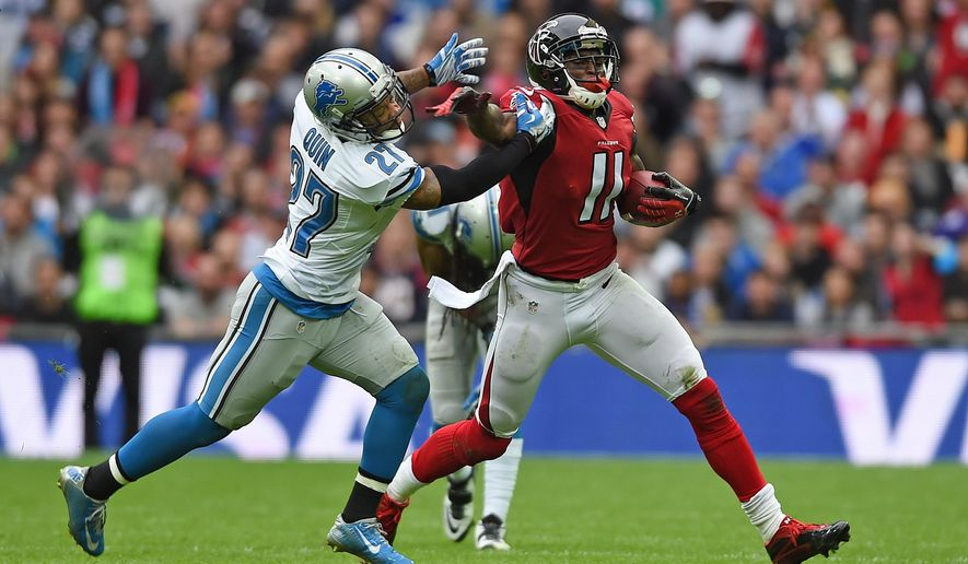 Detroit Lions free safety Glover Quin (27), left, tackles Atlanta Falcons wide receiver Julio Jones (11) during the NFL football game at Wembley Stadium, London, Sunday, Oct. 26, 2014.  (AP Photo/Tim Ireland)