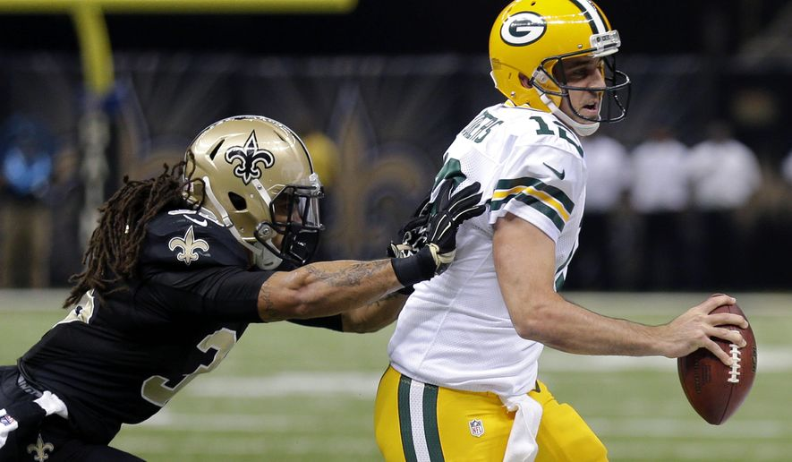 New Orleans Saints defensive back Marcus Ball (36) pushes Green Bay Packers quarterback Aaron Rodgers (12) out of bounds in the first half of an NFL football game in New Orleans, Sunday, Oct. 26, 2014. (AP Photo/Bill Haber)