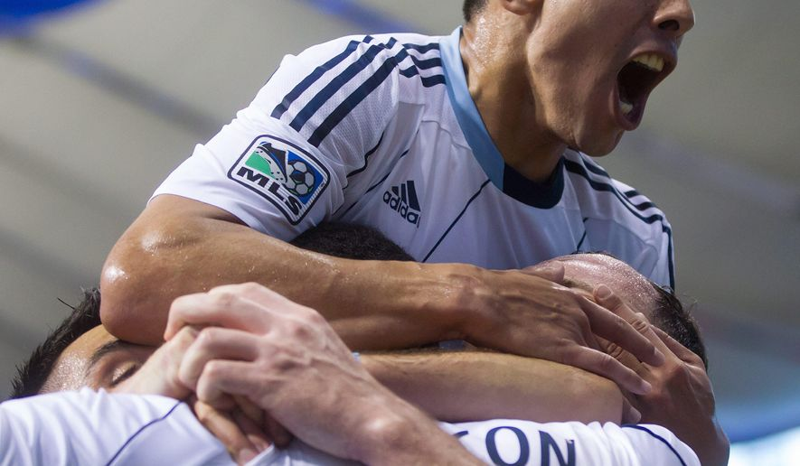 CORRECTS TO SEBASTIAN FERNANDEZ, INSTEAD OF PEDRO MORALES  - Vancouver Whitecaps' Sebastian Fernandez leaps on top of Kendall Watson after Watson scored against the Colorado Rapids during the second half of an MLS soccer game Saturday, Oct. 25, 2014, in Vancouver, British Columbia. (AP Photo/The Canadian Press, Darry Dyck)