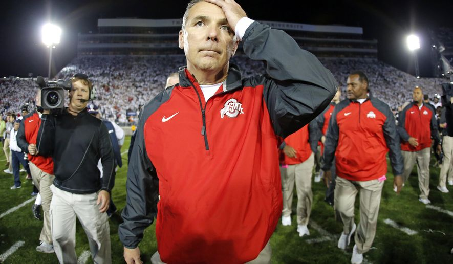 In this photo taken with a fisheye lens Ohio State coach Urban Meyer walks off the field after the team's 31-24 win in double overtime over Penn State in an NCAA college football game in State College, Pa., Sunday, Oct. 26, 2014. (AP Photo/Gene J. Puskar)