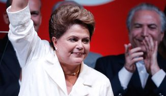 Brazil's President Dilma Rousseff celebrates her victory at a hotel in Brasilia, Brazil, Sunday, Oct. 26, 2014. Official results showed Sunday that President Rousseff defeated opposition candidate Aecio Neves of the Brazilian Social Democracy Party, and was re-elected Brazil's president. (AP Photo/Eraldo Peres)