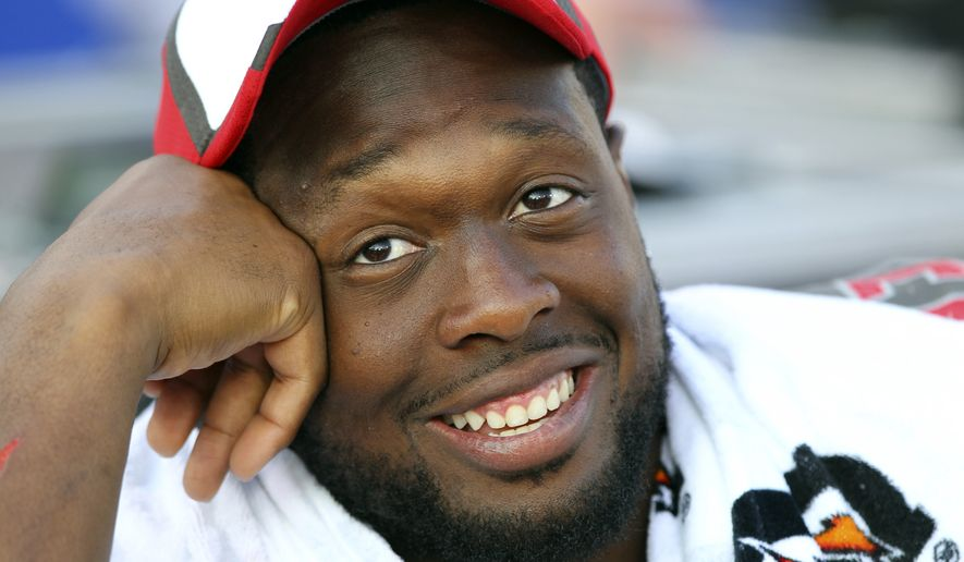 FILE - In this Aug. 23, 2014, file photo, Tampa Bay Buccaneers defensive tackle Gerald McCoy (93) watches his team play during the second half of a preseason NFL football game against the Buffalo Bills in Orchard Park, N.Y. McCoy has signed a seven-year extension with the Buccaneers worth $98 million, making him the highest-paid player at his position.   (AP Photo/Bill Wippert, File)