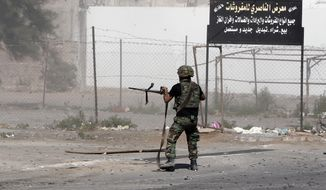 A Lebanese army soldier opens fire during clashes with Islamic militants in the northern port city of Tripoli, Lebanon, Sunday, Oct. 26, 2014. The Lebanese army brought tanks and commando forces into the northern city of Tripoli Sunday, where fighting with Muslim militants has intensified and spread to nearby areas. (AP Photo/Bilal Hussein)