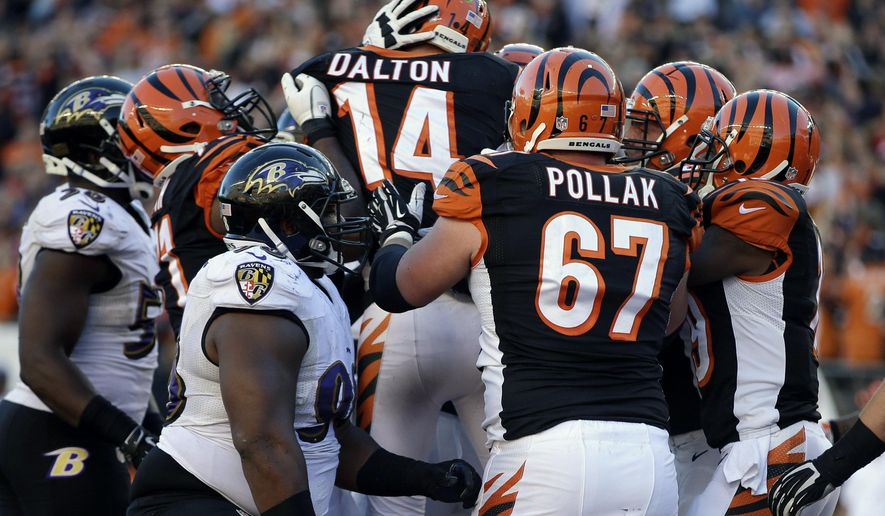 Cincinnati Bengals quarterback Andy Dalton (14) celebrates with teammates after scoring an NFL football game-winning touchdown against the Baltimore Ravens during the second half in Cincinnati, Sunday, Oct. 26, 2014. (AP Photo/Darron Cummings)