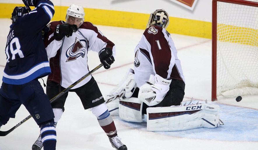 Winnipeg Jets' Bryan Little (18) scores the game winning goal in overtime as he beats Colorado Avalanche Tyson Barrie (4) and goaltender Semyon Varlamov (1) during NHL hockey action in Winnipeg, Manitoba, Sunday, Oct. 26, 2014. (AP Photo/The Canadian Press, Trevor Hagan)