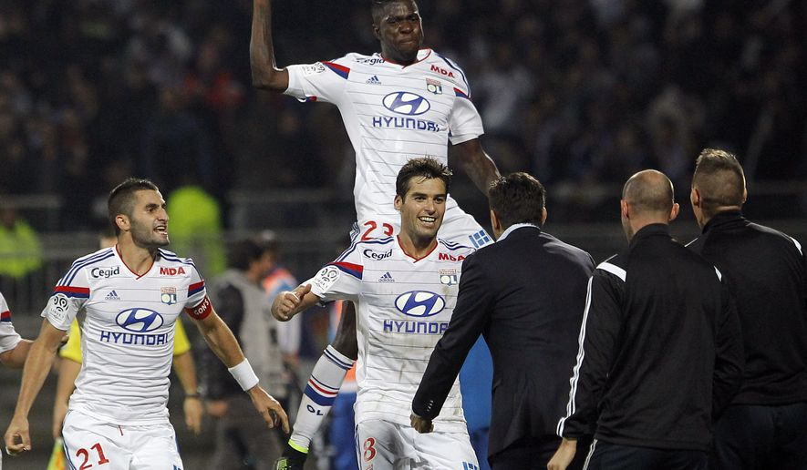 Lyon's Yoann Gourcuff, center, celebrates with his teammates after he scored a goal against Marseille during their French League One soccer match at Gerland stadium, in Lyon, central France, Sunday, Oct. 26, 2014. (AP Photo/Laurent Cipriani)