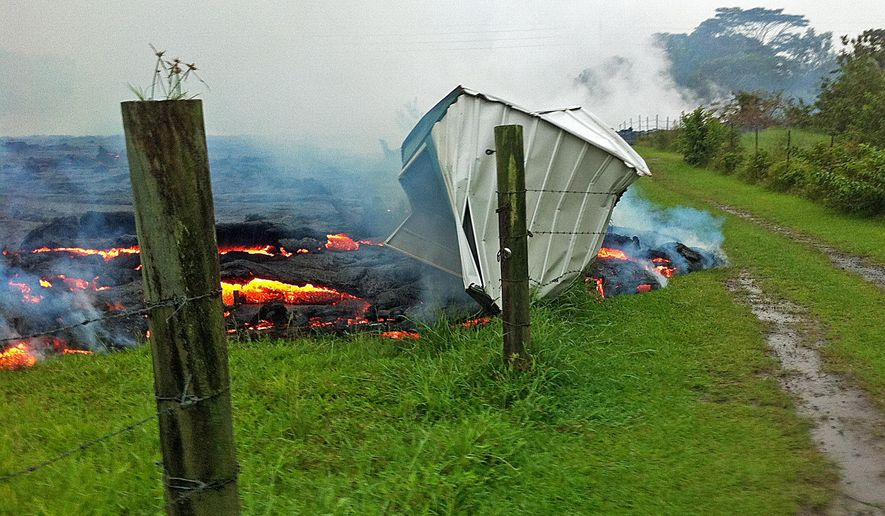 This Oct. 25, 2014 photo provided by the U.S. Geological Survey shows a small shed being consumed by lava in a pasture between the Pahoa cemetery and Apa?a Street near the town of Pahoa on the Big Island of Hawaii. Dozens of residents in this rural area of Hawaii were placed on alert as flowing lava continued to advance. Authorities on Sunday, Oct. 26, 2014 said lava had advanced about 250 yards since Saturday morning and was moving at the rate of about 10 to 15 yards an hour, consistent with its advancement in recent days. The flow front passed through a predominantly Buddhist cemetery, covering grave sites in the mostly rural region of Puna, and was roughly a half-mile from Pahoa Village Road, the main street of Pahoa. (AP Photo/U.S. Geological Survey)