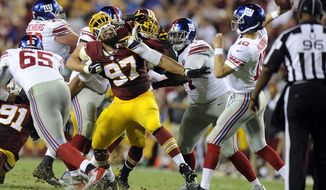 Washington Redskins defensive end Jason Hatcher (97) fights to get to New York Giants quarterback Eli Manning (10) in the third quarter at FedExField, Landover, Md., Sept. 25, 2014. (Preston Keres/Special for The Washington Times)