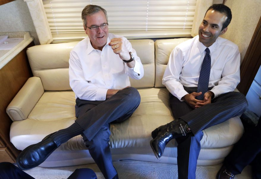 """This Oct. 14, 2014, file photo shows George P. Bush reacting as his dad, former Florida Gov. Jeb Bush, left, gives a fist pump during an interview in Abilene, Texas. The younger Bush said in an interview with ABC's """"This Week"""" Sunday, Oct. 26, 2014, that his dad is """"moving forward"""" on a potential 2016 White House run and it appears more likely he'll join the Republican presidential field. The former Florida governor declined to run for president in 2012 despite encouragement from Republicans. (AP Photo/LM Otero, File) ** FILE **"""
