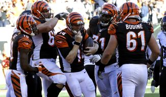 Cincinnati Bengals quarterback Andy Dalton, center, celebrates his last-minute touchdown with teammates during the second half of an NFL football game against the Baltimore Ravens in Cincinnati, Sunday, Oct. 26, 2014. (AP Photo/Al Behrman)
