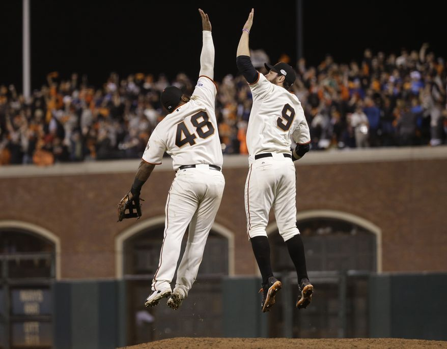 San Francisco Giants Pablo Sandoval, left, leaps up to high five Brandon Belt after defeating the Kansas City Royals 11-4 in Game 4 of baseball's World Series Saturday, Oct. 25, 2014, in San Francisco. (AP Photo/Matt Slocum)