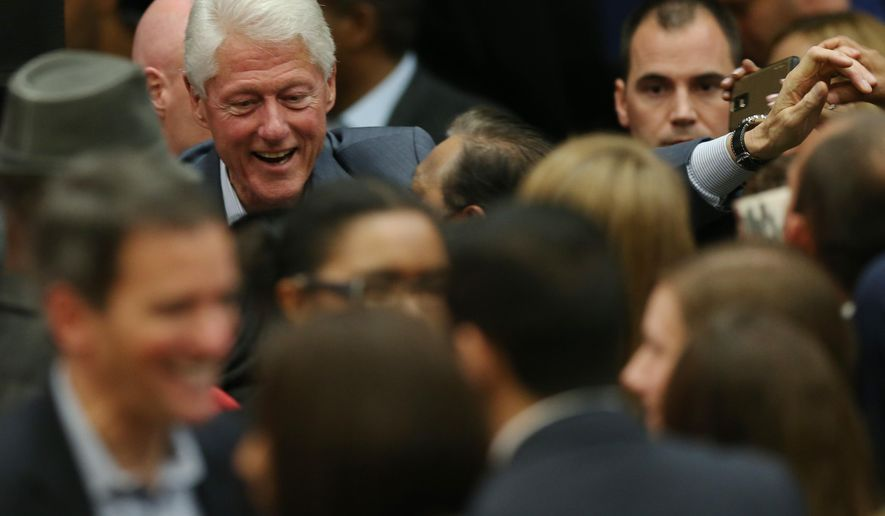 Former President Bill Clinton talks to voters while reaching out to other well-wishers while working the rope line following his appearance at a high school in Aurora, Colo., to promote Colorado's Democratic candidates in the upcoming general election on Monday, Oct. 27, 2014. (AP Photo/David Zalubowski)