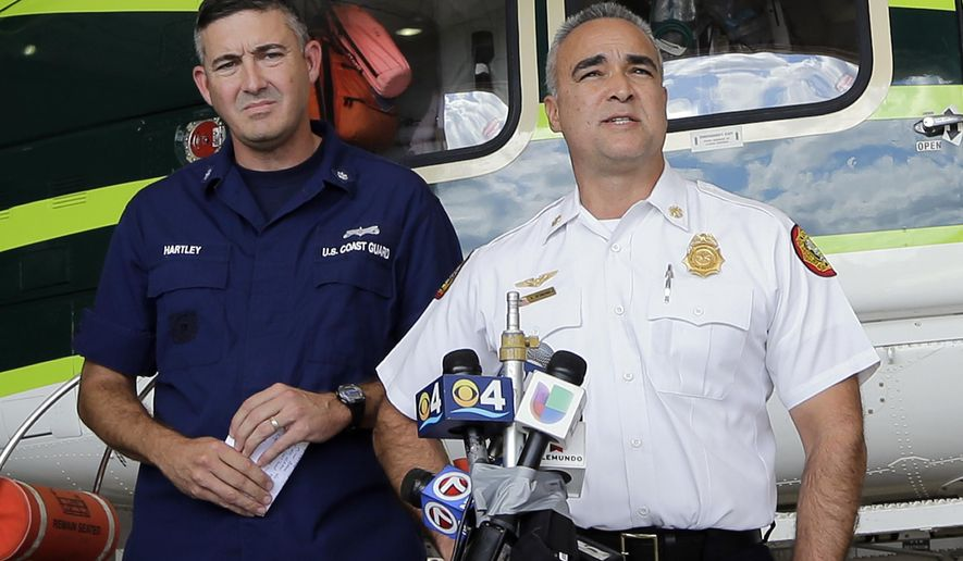Chief of Miami-Dade Air Resue Antonio Hernandez, right, talks to reporters during a news conference as U.S. Coast Guard commander Respond Sector Chief Richard Hartley, left, looks on, in Miami, Monday, Oct. 27, 2014. In total, ten Cuban migrants have been found and three more remain unaccounted for in the waters off Miami.   (AP Photo/Alan Diaz)