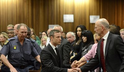 Oscar Pistorius, center, greets his uncle Arnold Pistorius, right, and other family members as he is led down to the cells of the court in Pretoria, South Africa, Tuesday, Oct. 21, 2014. Pistorius received a five-year prison sentence for culpable homicide by judge Thokozile Masipais for the killing of his girlfriend Reeva Steenkamp. (AP Photo/Herman Verwey, Pool)